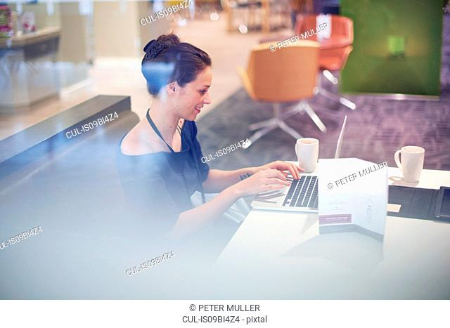Businesswoman sitting in airport lounge, using laptop, smiling