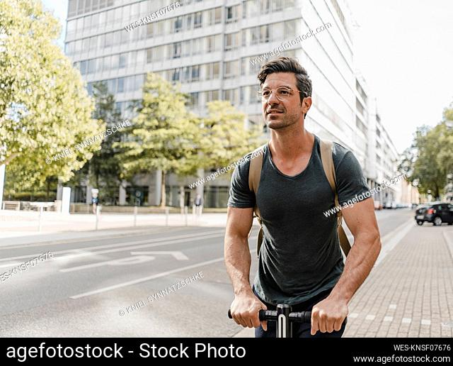 Casual man riding e-scooter in the city
