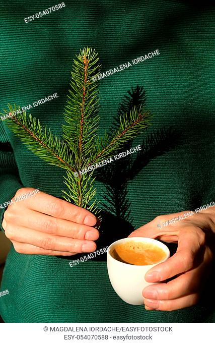 Woman is holding pine tree branch and an espresso cup