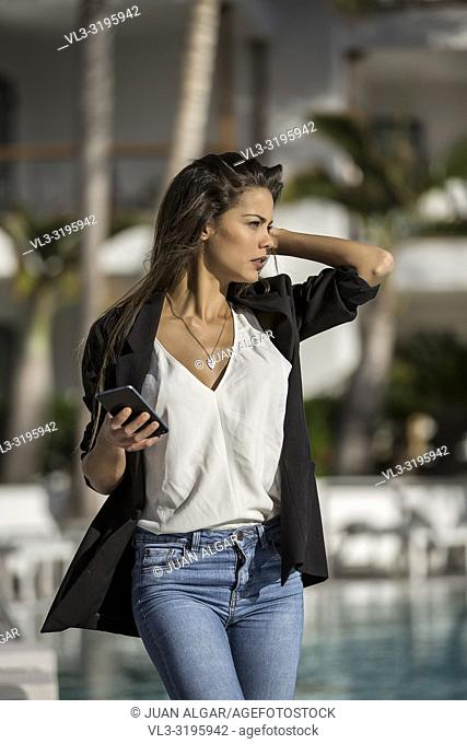 Stylish businesswoman in black jacket holding smartphone and walking on poolside in sunlight