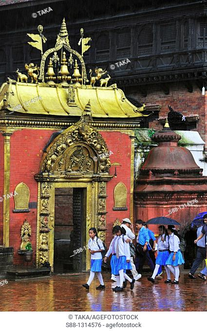School girls going back home on the rainy day passing by Golden Gate in Durbar Square UNESCO World heritage site