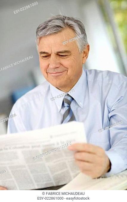 Portrait of senior businessman reading newspaper