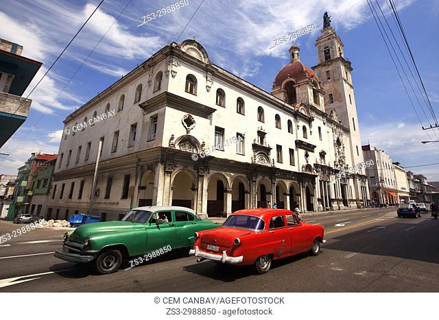 Old American cars used as taxi in front of the Church and Convent of Carmen-Iglesia y Convento Del Carmen in Vedado district, La Habana, Cuba, West Indies