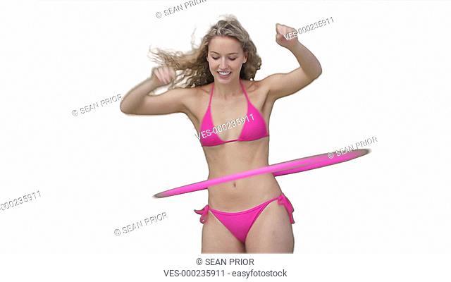 Junge h?bsche Frau im Bikini mit langen blonden Haaren schwingt lachend einen rosa Reifen um ihre H?ften