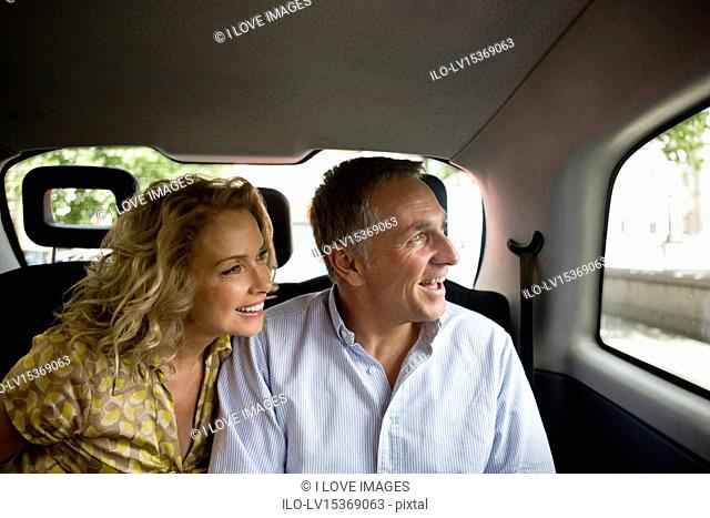A middle-aged couple in a London taxi, admiring the view