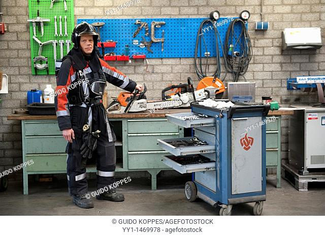 Tilburg, Netherlands. Firefighter in fireproof turnout gear on his regular job inside the barracks