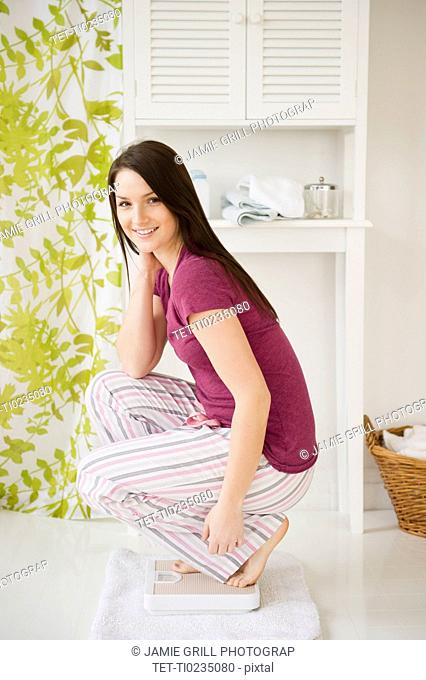 Young woman in pajamas crouching on scale