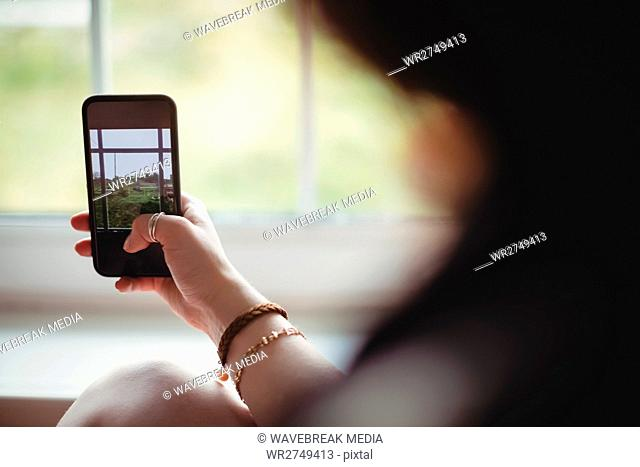 Woman taking a photo on the mobile phone from window