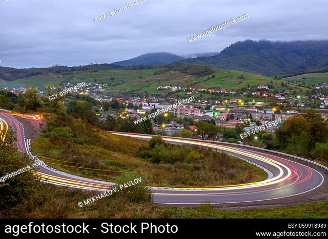 Cloudy evening on a mountain road. Headlight trails of fast moving cars. A small village shines with lights in the valley