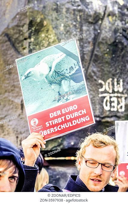 junger mann trägt ein plakat mit der aufschrift -der euro stirbt durch überschuldung - , demonstration gegen die macht der finanzmärkte in stuttgart