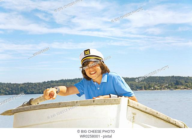 Boy wearing ship captains hat in row boat