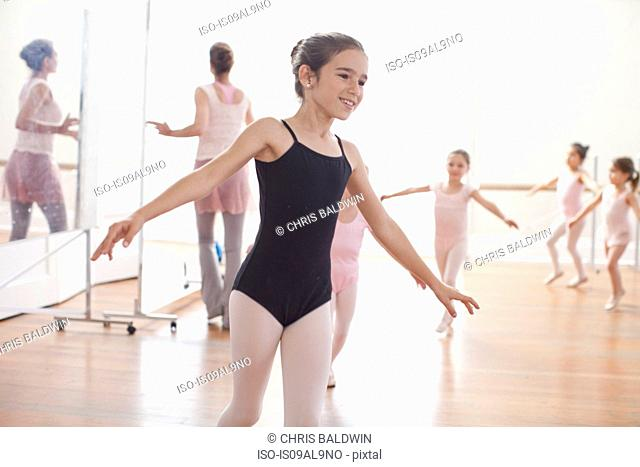 Teacher and girls practicing ballet dancing in ballet school