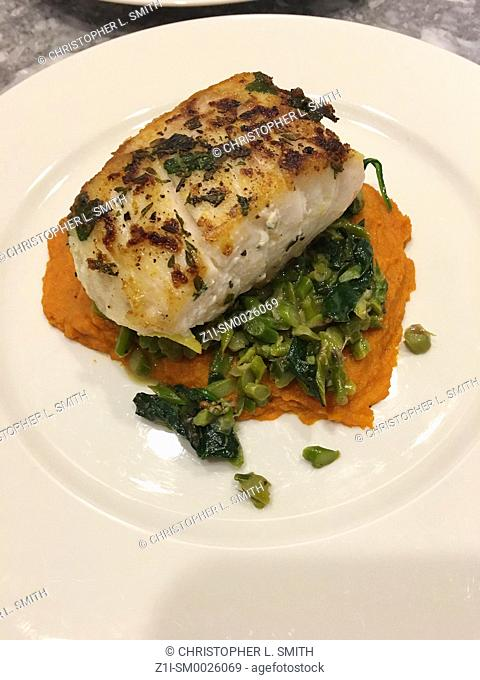 Baked cod on a puree of Sweet Potato and green beans on a white plate