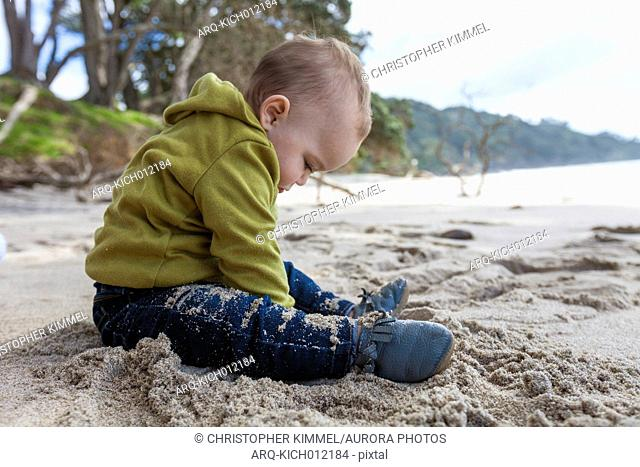 Young boy sitting at Waihi Beach in Orokawa Scenic Reserve, New Zealand
