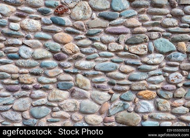 Wall with colorful cemented pebbles. It can be used as background