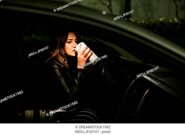 Young woman with disposable cup and camera in a car at night