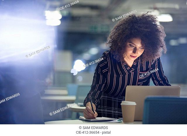Focused businesswoman working late at laptop, taking notes in dark office