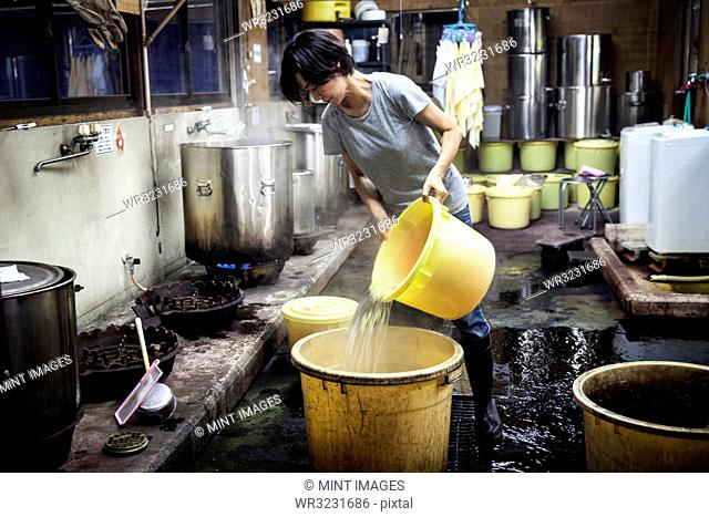 Japanese woman working in a textile plant dye workshop, pouring hot water into yellow plastic buckets