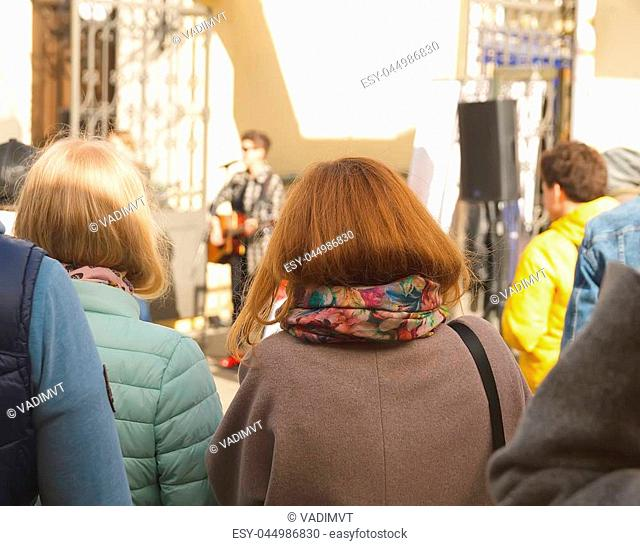 Girl listens and looks at street musicians
