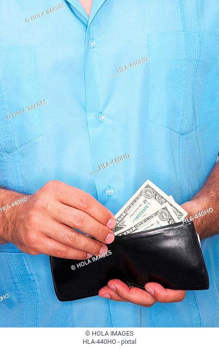 Mid section view of a man taking out money from a wallet