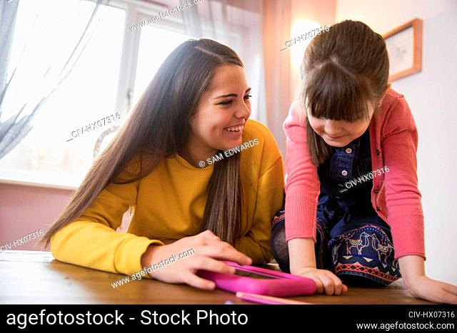Happy sisters using digital tablet at table