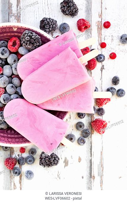 Homemade wild-berry ice lollies with raspberries, blueberries, red currants and blackberries in a bowl