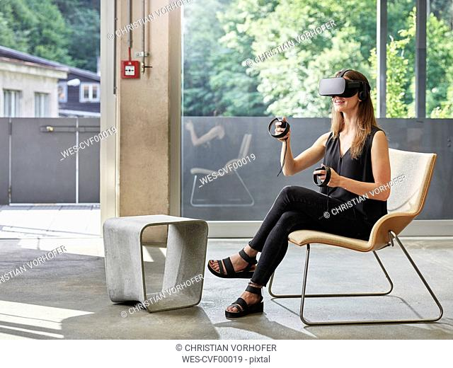 Smiling woman wearing VR glasses sitting on chair