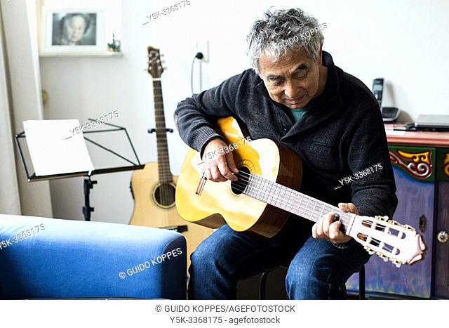 Tilburg, Netherlands. Senior adult Indonesian male playing his guitar inside his residential living room to prepare for a private, domestic concert