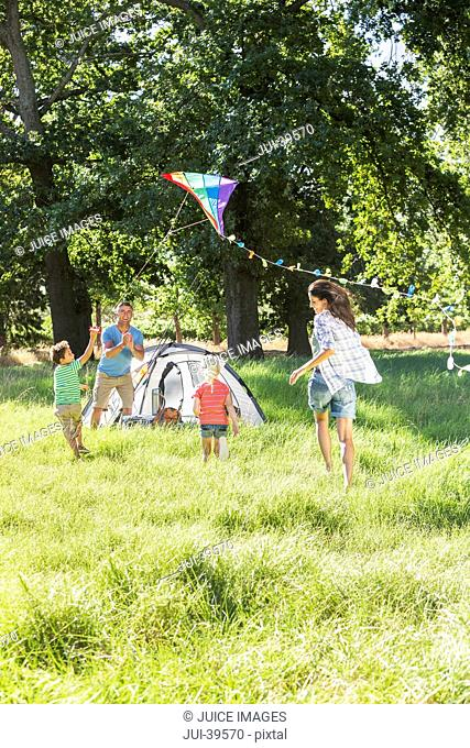 Family Flying Kite On Camping Holiday In Countryside