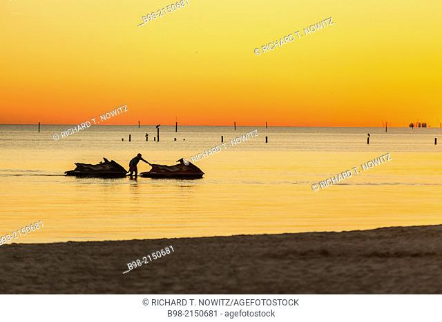 A lone person is in the water after sunset in Gulf of Mexico in Biloxi, Mississippi