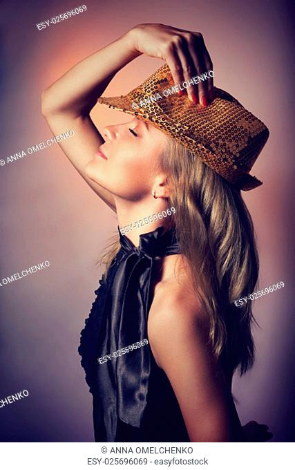 .Side view of beautiful woman dancing in night club, closing eyes of pleasure, wearing stylish shiny hat, celebrating new year holiday