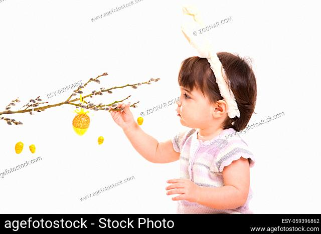 Baby girl in easter bunny costume, playing with easter eggs hanging from willow branch. Isolated on white background