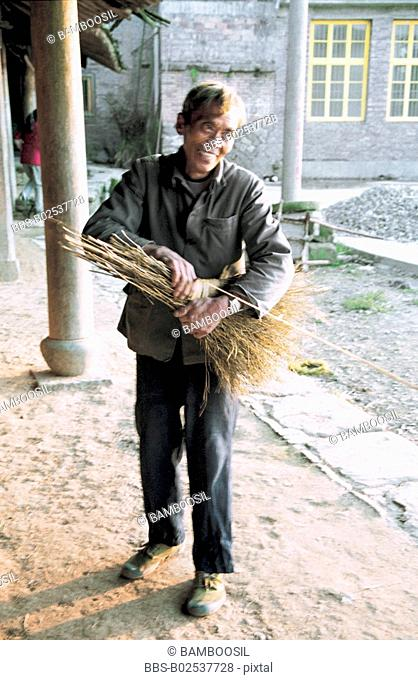 View of a cheerful mature man making broom, Taishun County, Zhejiang Province, People's Republic of China
