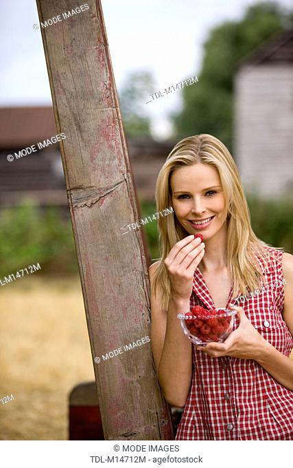 A woman eating a bowl of raspberries, outdoors