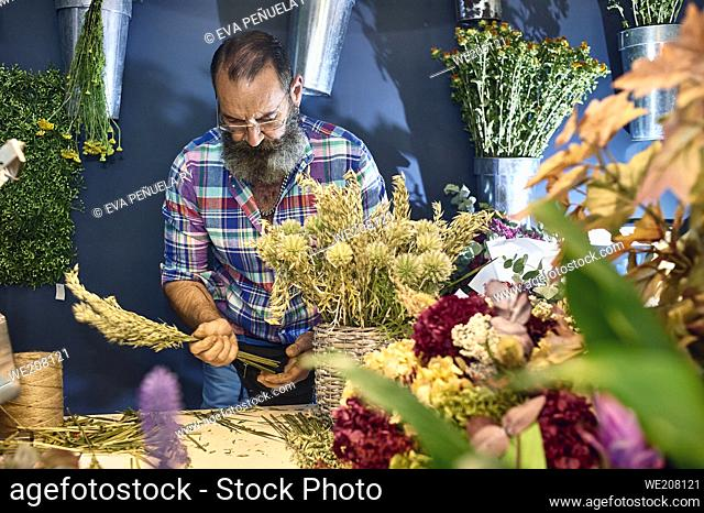 A florist taking care of various flowers and bouquets in his shop