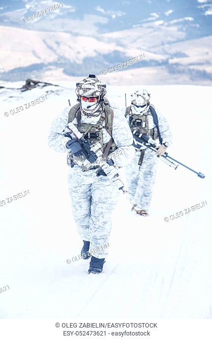 Army servicemen in winter camo somewhere in the mountains. Walking moving across snow desert despite bad weather wind and cold