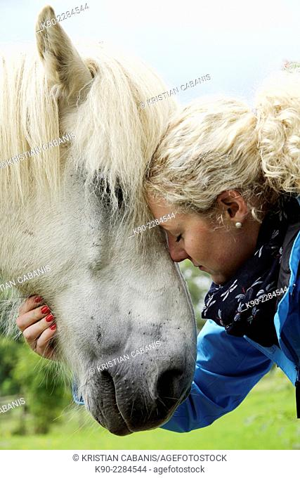 Caucasian woman taking care of a white Icelandic horse, Attenbach, Bergneustadt, North Rhine-Westphalia, Germany, Europe