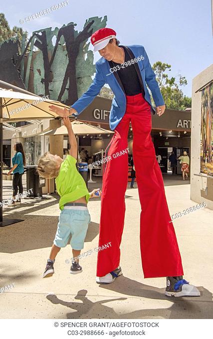 A costumed stilt walker shares a high five with an exuberant boy toddler at an art festival in Laguna Beach, CA