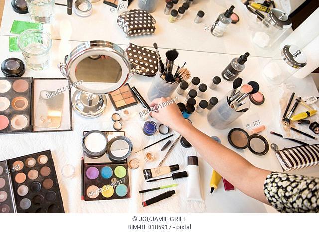 Hispanic woman selecting makeup from table