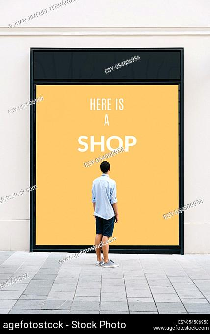 Young man from behind in front of store showcase with text: Here is a Shop