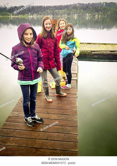 Girls fishing off wooden dock