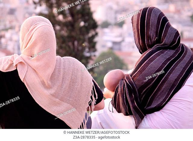 A mother breastfeeding her baby on top of the Areaopagus hill in Athens, Greece
