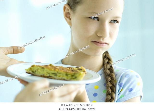 Hands holding up slice of quiche toward girl, girl making face and looking away