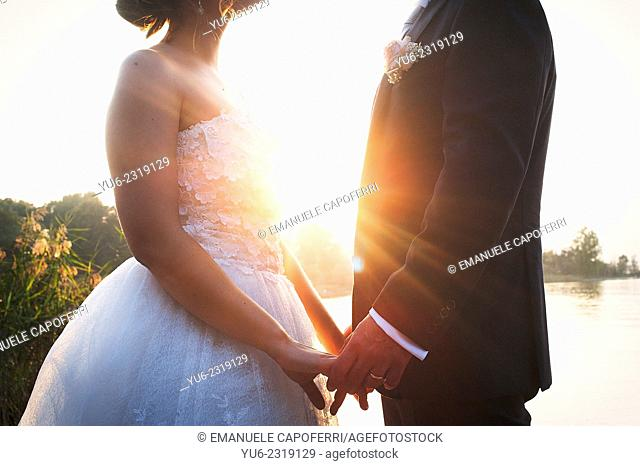 Wedding couple at sunset holding hands