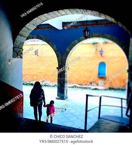 A woman carries her daughter inside a church's patio in San Angel, Mexico City, Mexico