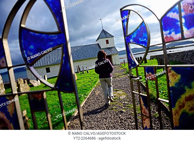 Young woman visits Saint Olav's church in Kirkjubøur, Faroe Islands