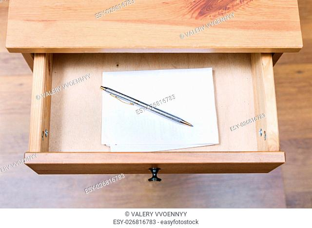 top view of folded note and pen in open drawer of nightstand