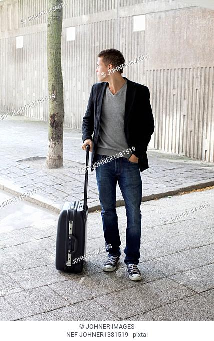 Young man with suitcase standing on sidewalk