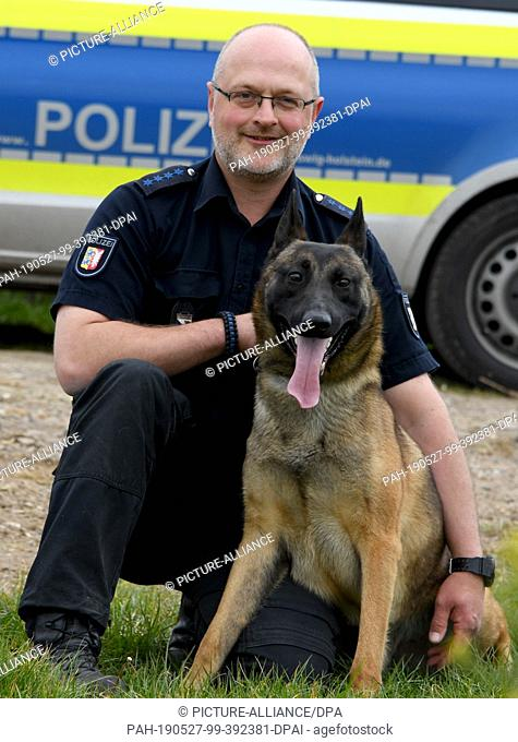 """16 May 2019, Schleswig-Holstein, Silberstedt: Mongrel dog """"""""Jack"""""""" sits next to his master Hauke Messer. The dog had been abandoned as a puppy"""