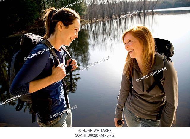 Two women laughing beside lake